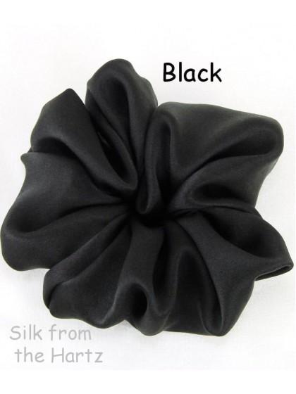 An elegant, large solid black silk satin hair scrunchie accessory for girls or women that won't damage long hair.